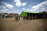 Students run across the yard of the for-profit Bridge International Academy in the Nairobi slum of Mukuru kwa Njenga.