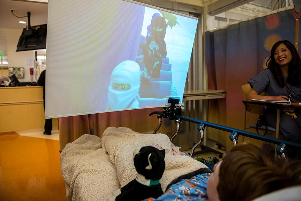 "Kids waiting for surgery at the hospital can choose from a menu of age-appropriate entertainment options that include certain TV shows, movies and music videos. The big, close screen helps make the experience ""immersive,"" the doctors who designed it say."