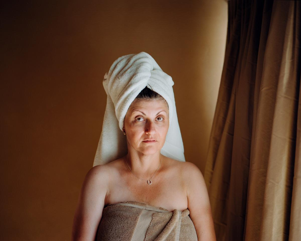 Moscovitch's parents said goodbye to Israel after they got married. On her one-way flight to Los Angeles, Imma carried a jumbled archive of family photos. Those photos are all she has of her mother. Here, Imma stands for a portrait after a shower on April