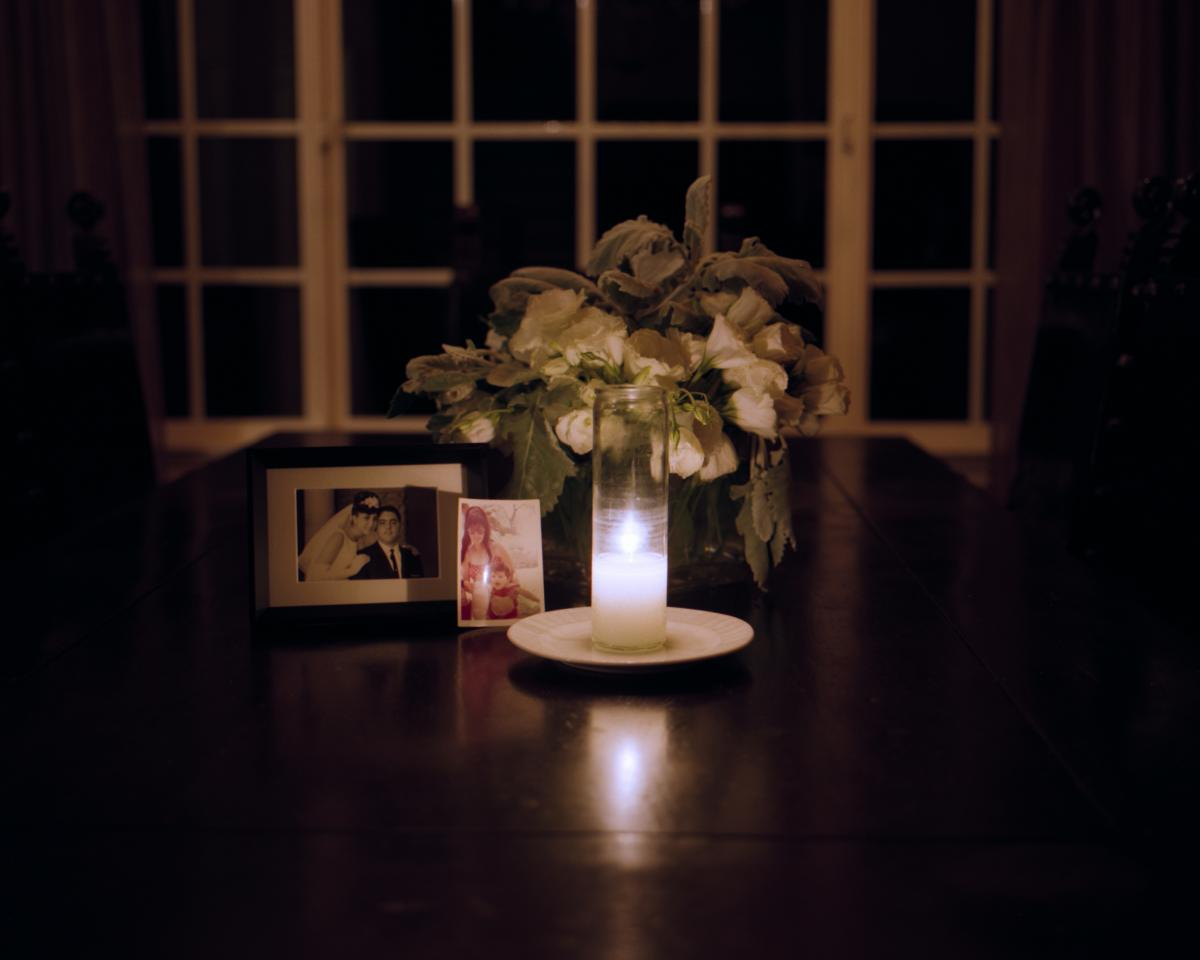 In Jewish tradition, family members will often light a memorial candle non-stop for one year after a death. Every Sunday, Imma makes a new bouquet to accompany the candle. Here, an array of old photographs are illuminated by the candlelight on May 8.