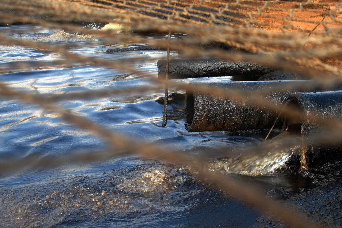 Dirty water from the oil wells flows through oil-caked pipes into a settling pit where trucks vacuum off the oil. A net covers the pit to keep out birds and other wildlife. Streams of this wastewater flow through the reservation and join natural creeks an