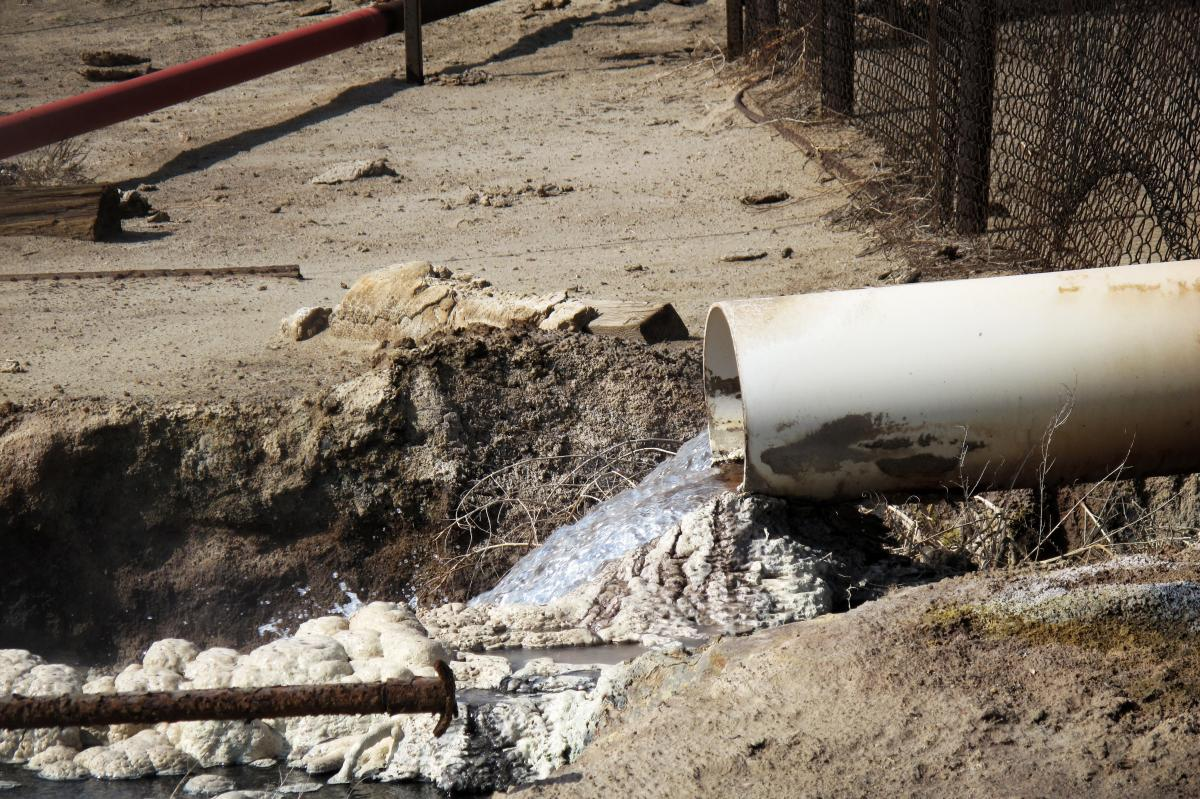 Internal EPA documents released to NPR show some EPA staffers have been trying to figure out what is in the wastewater released by oil companies. There are lots of chemicals. Some leave solid residues like these white and gray mounds. Danger signs near th