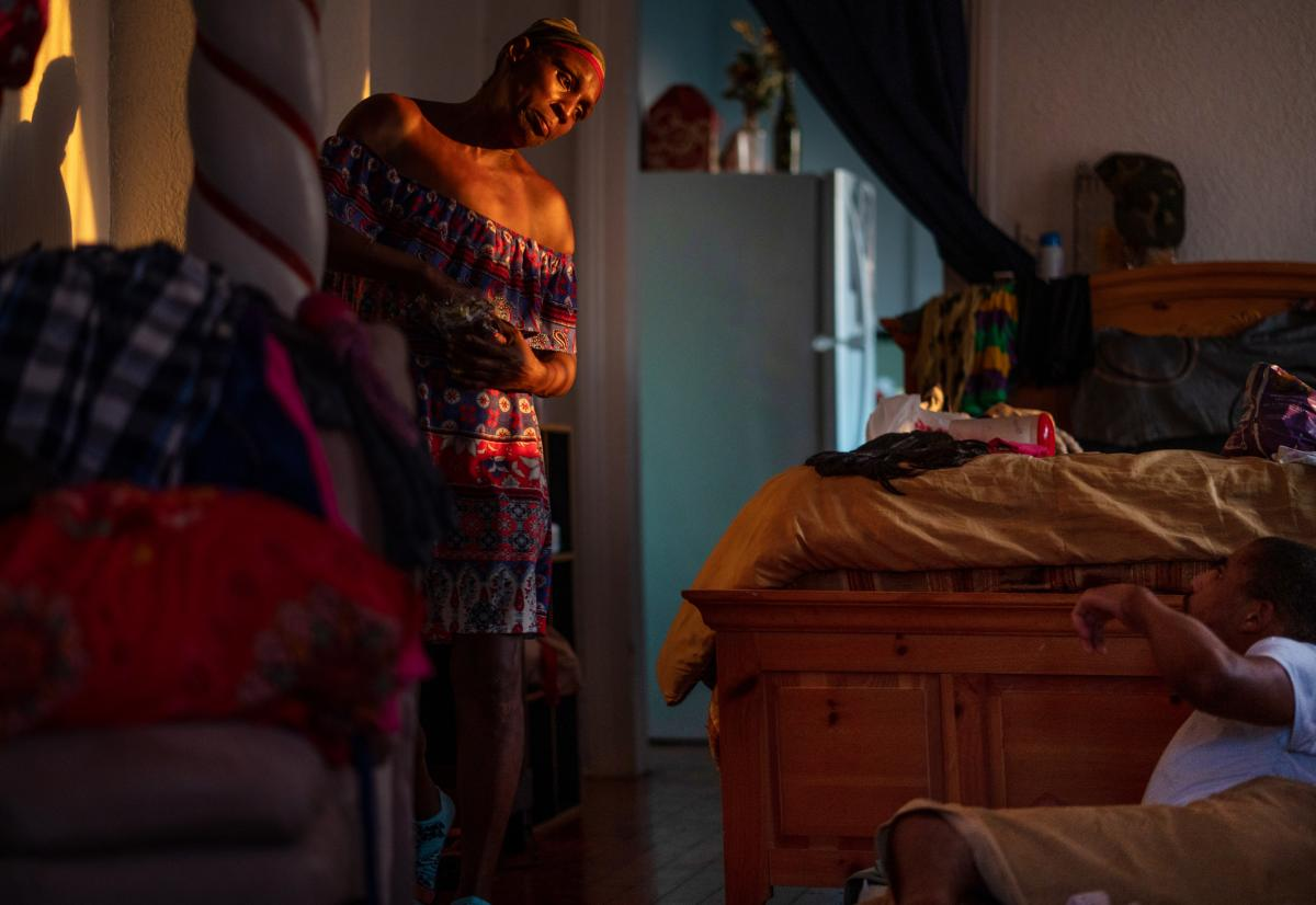 Grace Hollins packs as she prepares to take her son, Carl, on a Greyhound bus to Atlanta, where they'll have access to electricity and she'll be able to provide better care.