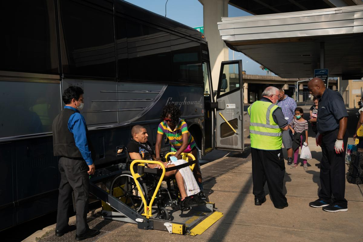 Hollins helps her son as he is lifted into the bus.