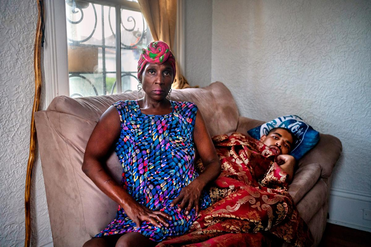 Grace Hollins and her son, Carl Hollins, who has cerebral palsy, at their home in New Orleans. Carl increasingly suffered in the severe heat in their apartment when electricity was out the week after Hurricane Ida.