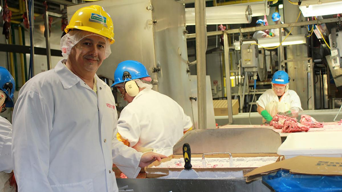 Todd Scherbing, Smithfield Foods' senior director of rendering, holds a tray of pituitary glands that are cut from hogs on the line at the Farmland Foods plant in Milan, Mo.