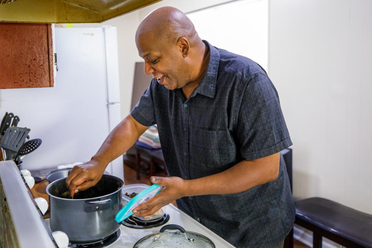 Gregory Curry makes dinner for his mother. Seen here on Sunday he packs a meal of fried chicken, collard greens, macaroni and tuna salad and cornbread, to take to her in the nursing home some 30 miles away.