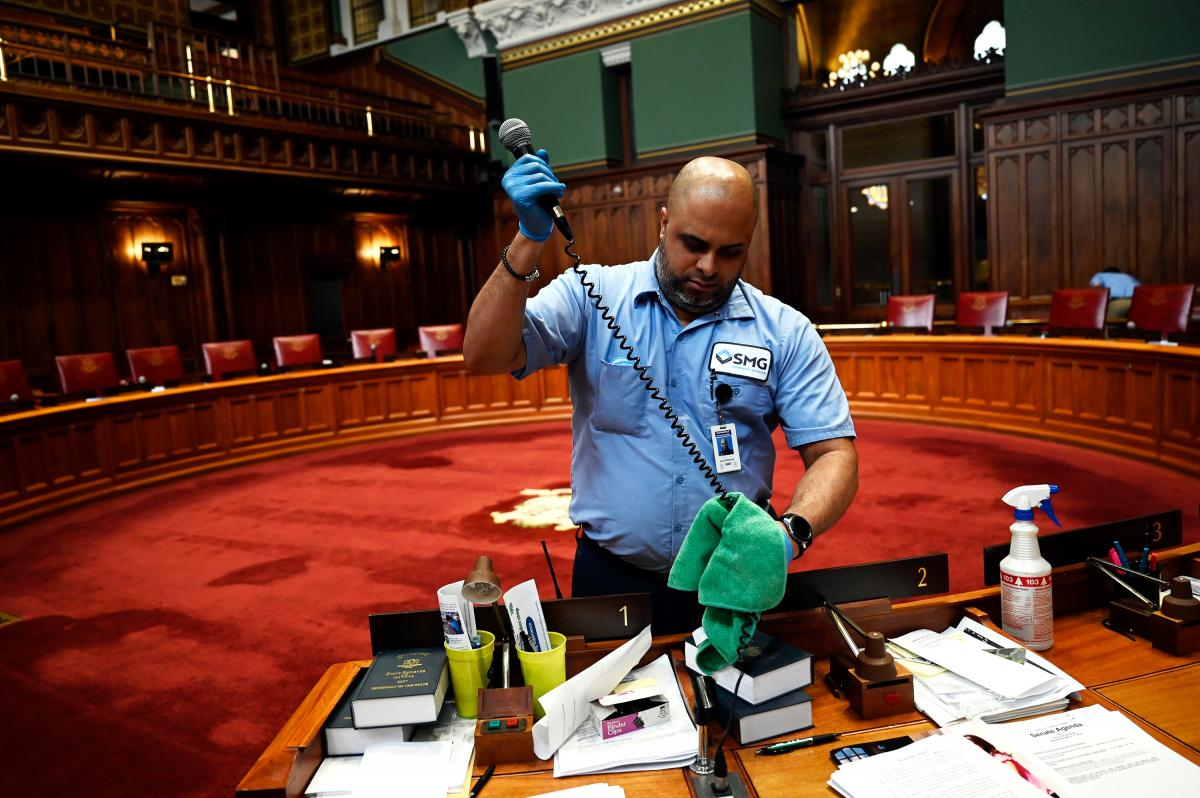 Connecticut's legislature is suspended until at least April 12 to follow the state's social distancing guidelines. Day porter Luis Almenas disinfected all the microphones during a deep clean in the Senate chambers on March 12.