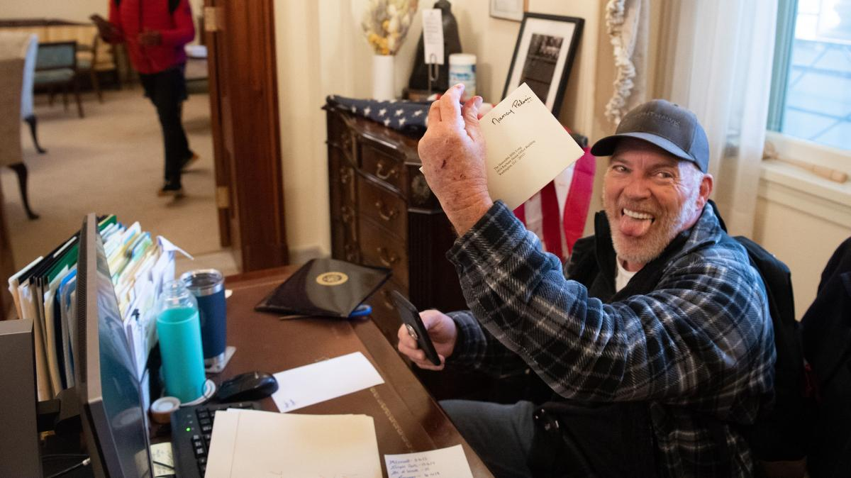 Richard Barnett, a supporter of President Trump, holds a piece of mail as he sits inside the office of Speaker of the House Nancy Pelosi after protesters breached the U.S. Capitol in Washington, D.C., on Jan. 6.