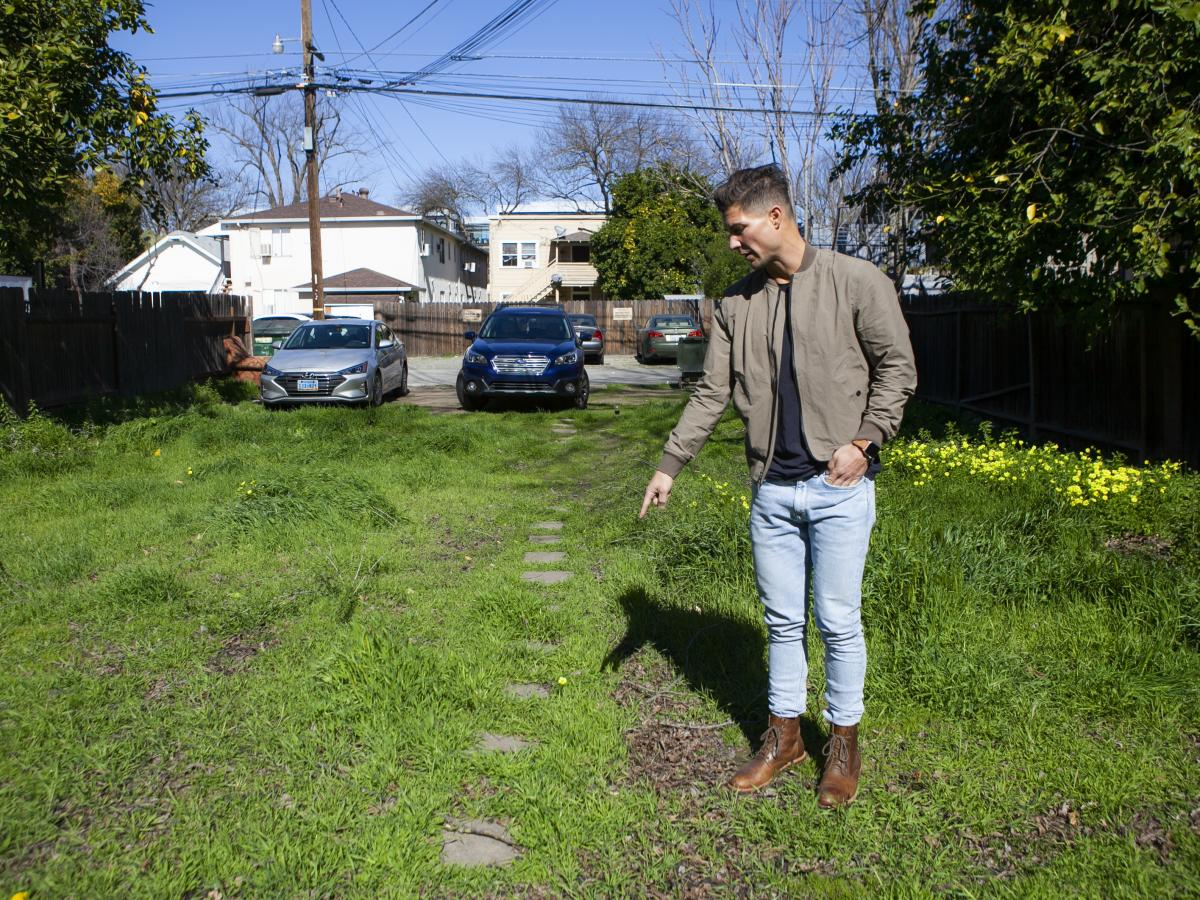 Real estate developer Kevin Khasigian points out the edges of what he hopes will one-day be a four-unit apartment building on what is now a grassy lot near Sacramento's downtown