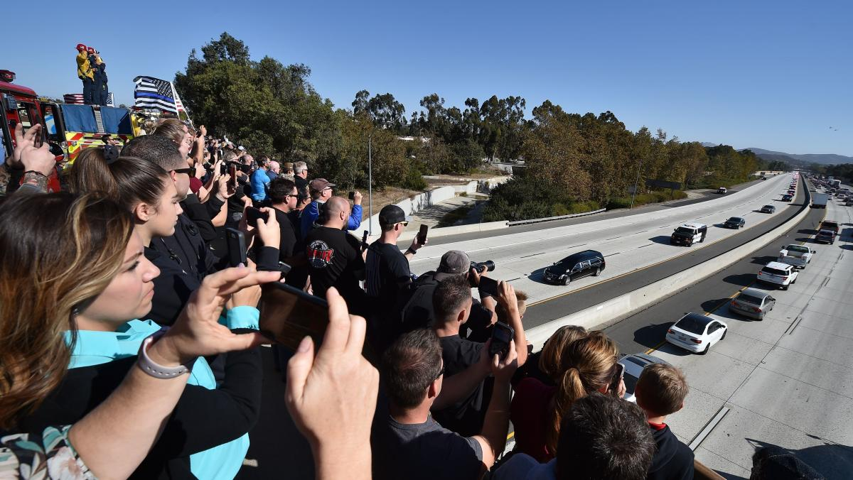 Firefighters, law enforcement and members of the public watch Thursday as a motorcade escorts Sgt. Ron Helus' body to the Ventura County Medical Examiner's Office.