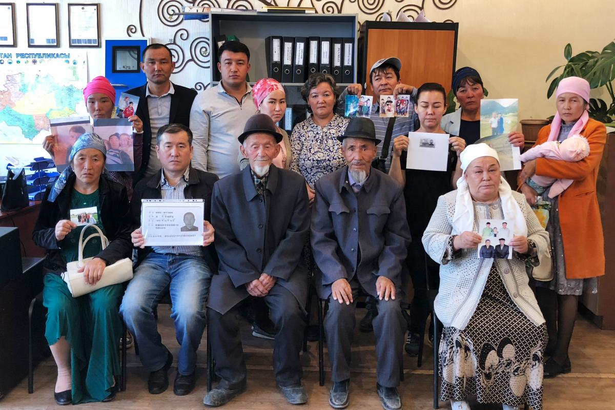 A group of ethnic Kazkhs stand together at the offices of Atazhurt in Almaty, displaying photos of their missing loved ones in the Xinjiang region of China, where government officials have rounded up the mostly Muslim ethnic minorities of the region and p