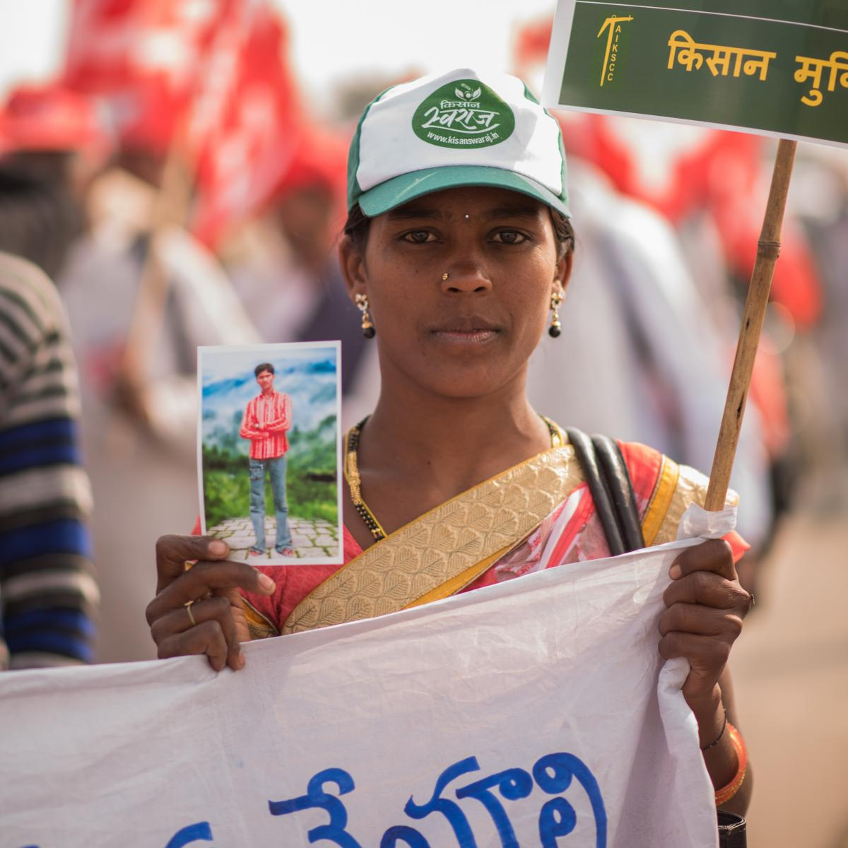 Surya Raga, a cotton farmer from Telangana, holding her husband's photo. He killed himself in 2014, after being unable to repay his loans.
