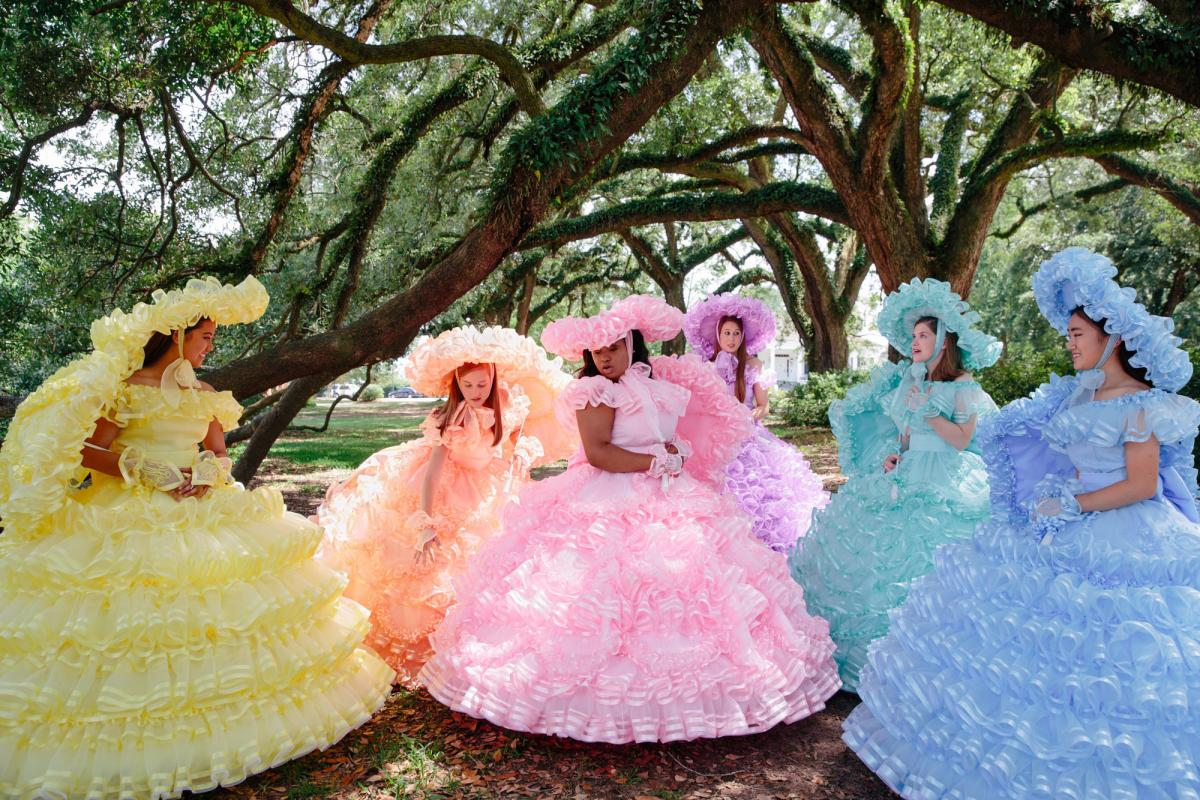 Six of the 50 Azalea Trail Maids gather under oak trees. The dresses come in six different colors, but only the queen of the court wears pink.