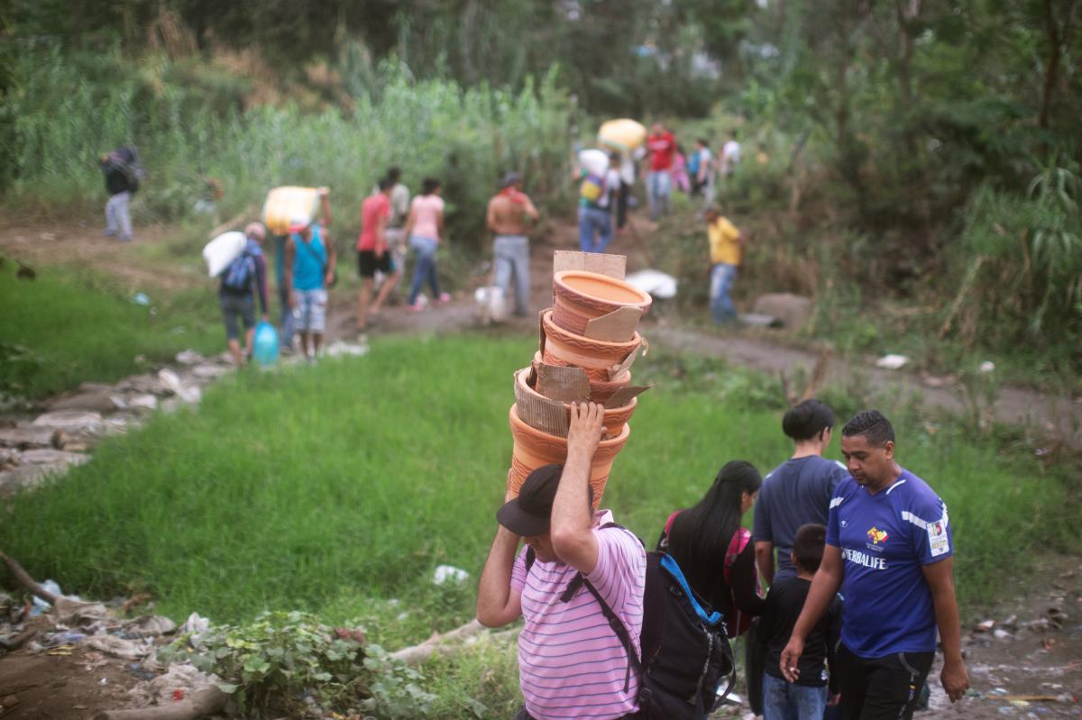 People walk from Venezuela to Colombia through an unauthorized border crossing in Villa del Rosario, Colombia. Some 3.4 million Venezuelans are seeking refuge abroad, with more than 1 million of them in neighboring Colombia, according to the United Nation