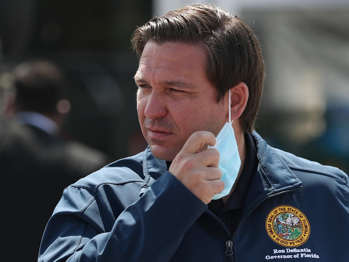 Florida Gov. Ron DeSantis takes his mask off as he prepares to speak during a press conference at the Hard Rock Stadium testing site in Miami Gardens, Fla., in May 2020.