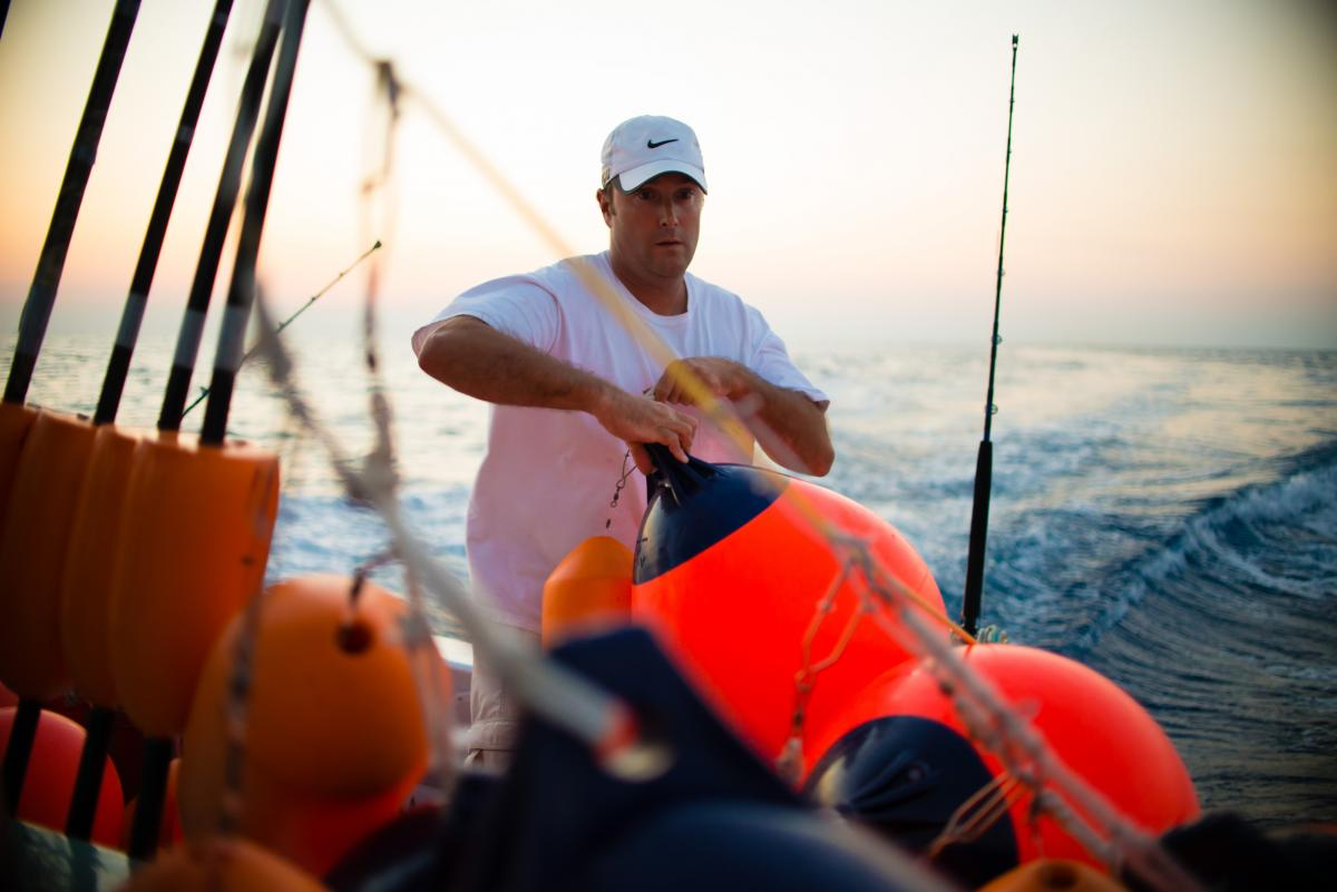 Manganello sets buoys while swordfishing with Palmer. They usually fish with 10-12 buoys that stretch for a mile or two, which have to be repeatedly checked throughout the night for bites.