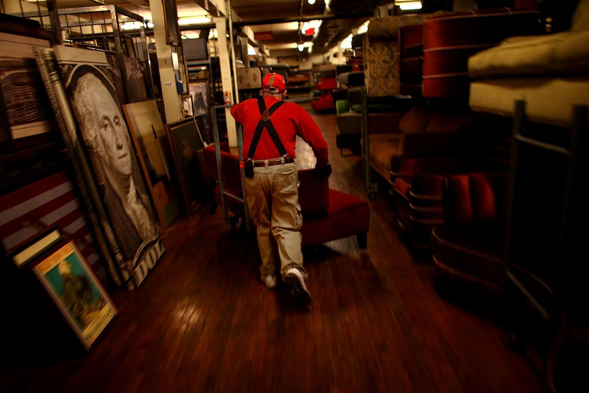 """Warner Brothers worker Stephen Lampke moves furniture on the Prop House's second floor, which holds the """"contemporary"""" items: sofas, coffee tables, end tables, bookcases, mostly middle-class workaday furniture."""