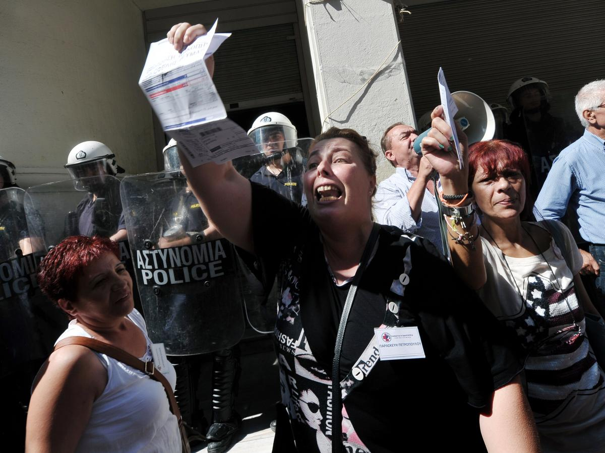 Unpaid for five months, nurse Paraskevi Petropoulou holds her unpaid electricity bill outside the Ministry of Health in Athens during an anti-government protest on Sept. 28, 2012.