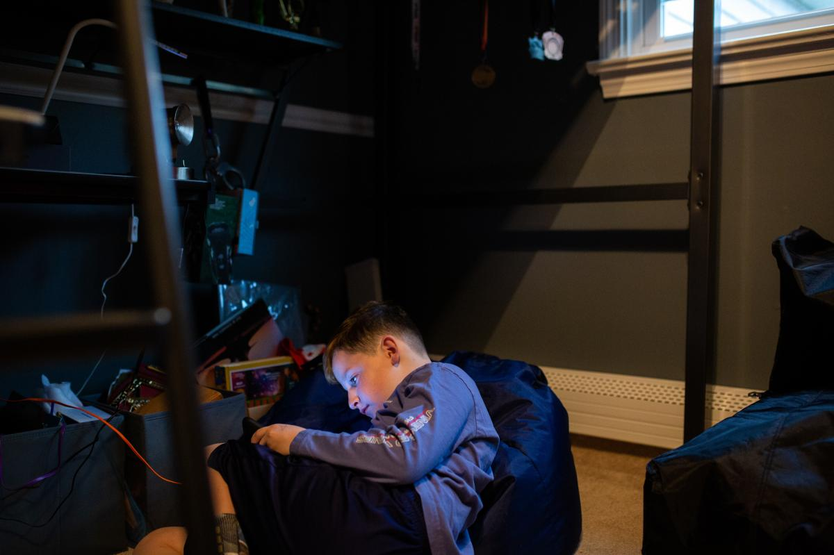 Joseph Calise, 9, plays on his iPad in his bedroom. Joseph used to get anxious whenever he was alone, even when taking a shower or at bedtime, so his parents, Jessica and Chris Calise, learned new parenting skills from the Yale Child Study Center.