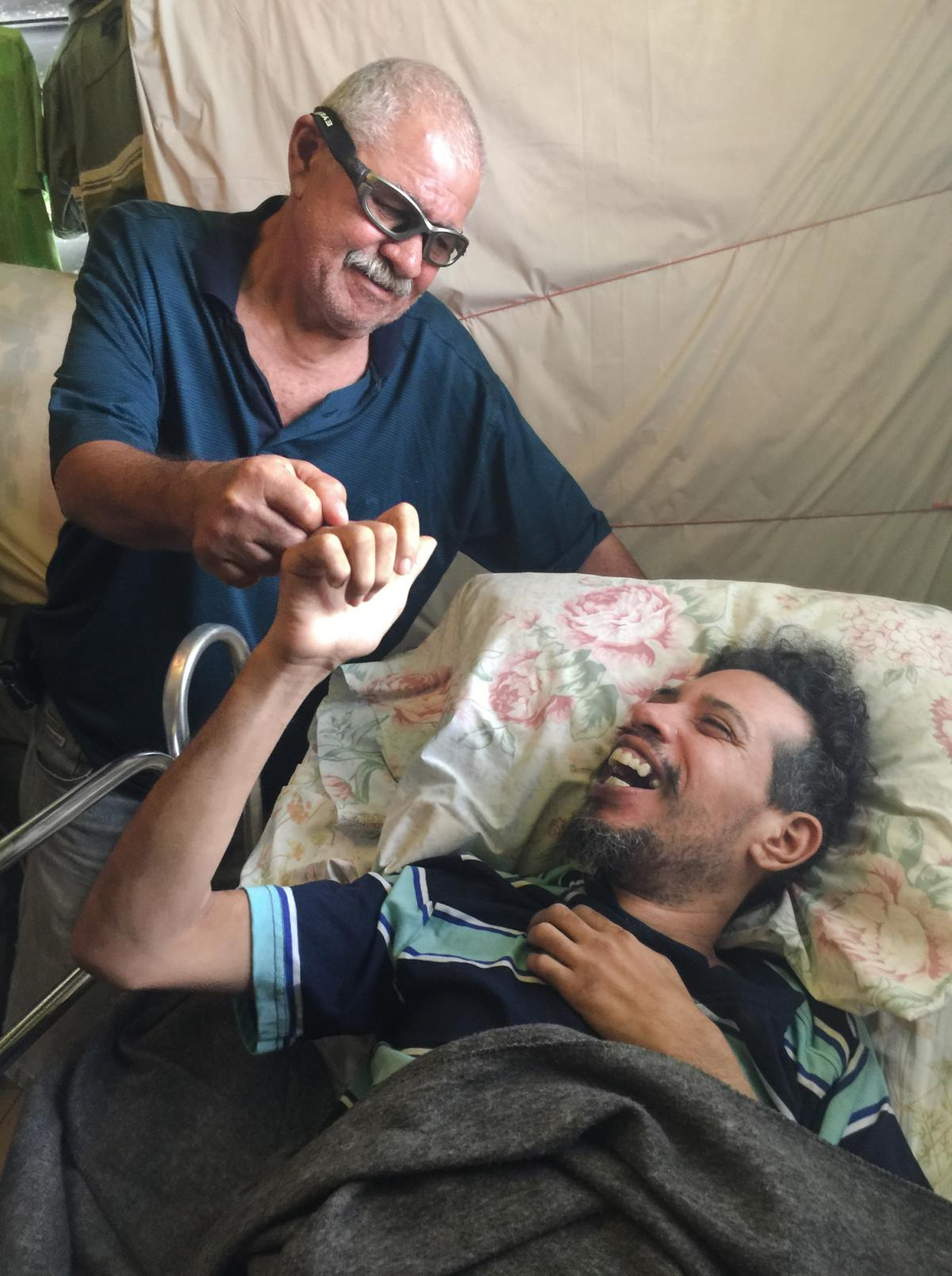 Osvaldo Martinez (left) takes care of his increasingly disabled son, Osvaldo Daniel Martinez, who is on Medicaid. With few neurologists on the island, they have not been able to get the younger Martinez an appointment with a specialist who could formally