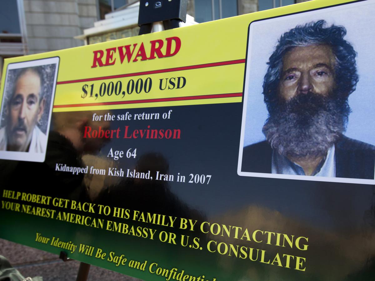 An FBI poster from 2012 shows a composite image (right) of former FBI agent Robert Levinson depicting how he would look after five years in captivity. The poster includes another image taken from a video released by his kidnappers.