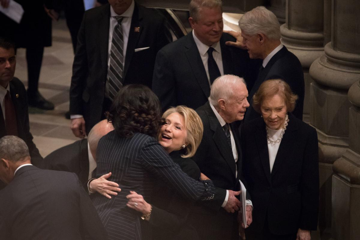 Former First Ladies Michelle Obama and Hillary Clinton hug before the funeral.