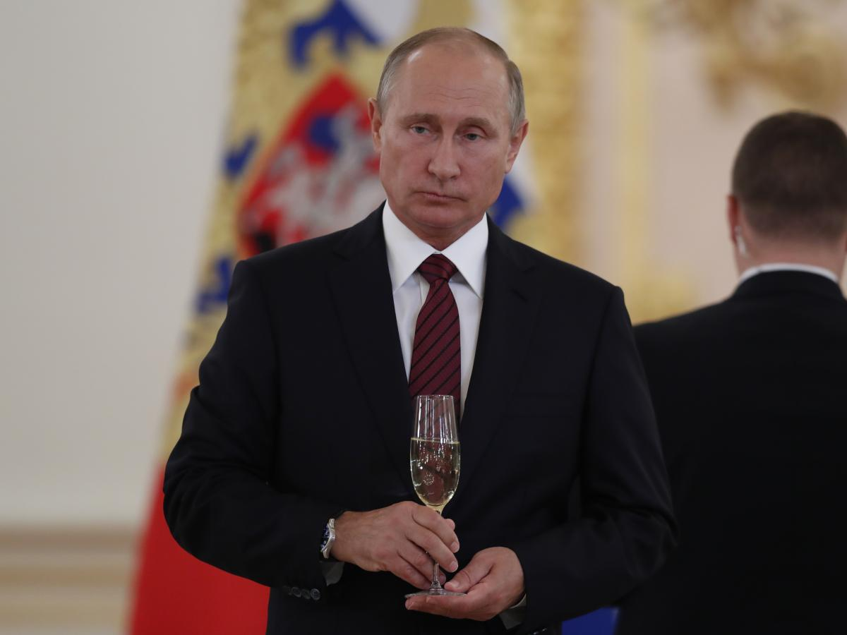 """Russian President Vladimir Putin holds a glass of Soviet Champagne during a Kremlin ceremony in 2017. A new Russian law says only Russian sparkling wine may be sold in Russia as """"champagne."""""""