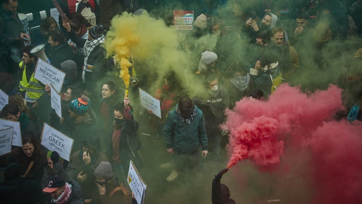 Protesters brandish colored flares during a rally Thursday in Paris as part of one of France's largest nationwide strikes in years. President Emmanuel Macron's intended changes to the pension system are facing resistance from transportation workers, teach