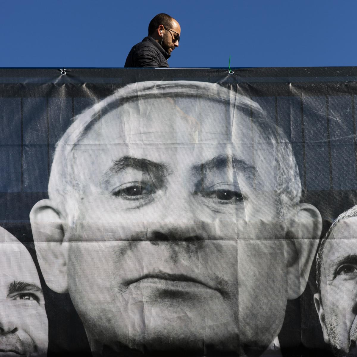 A man walks next to election campaign billboard for Blue and White party, shows Israeli Prime Minister Benjamin Netanyahu, flanked by party members, Amir Ohana, left and Rafi Peretz, right, in Tel Aviv, Israel, on Sunday.