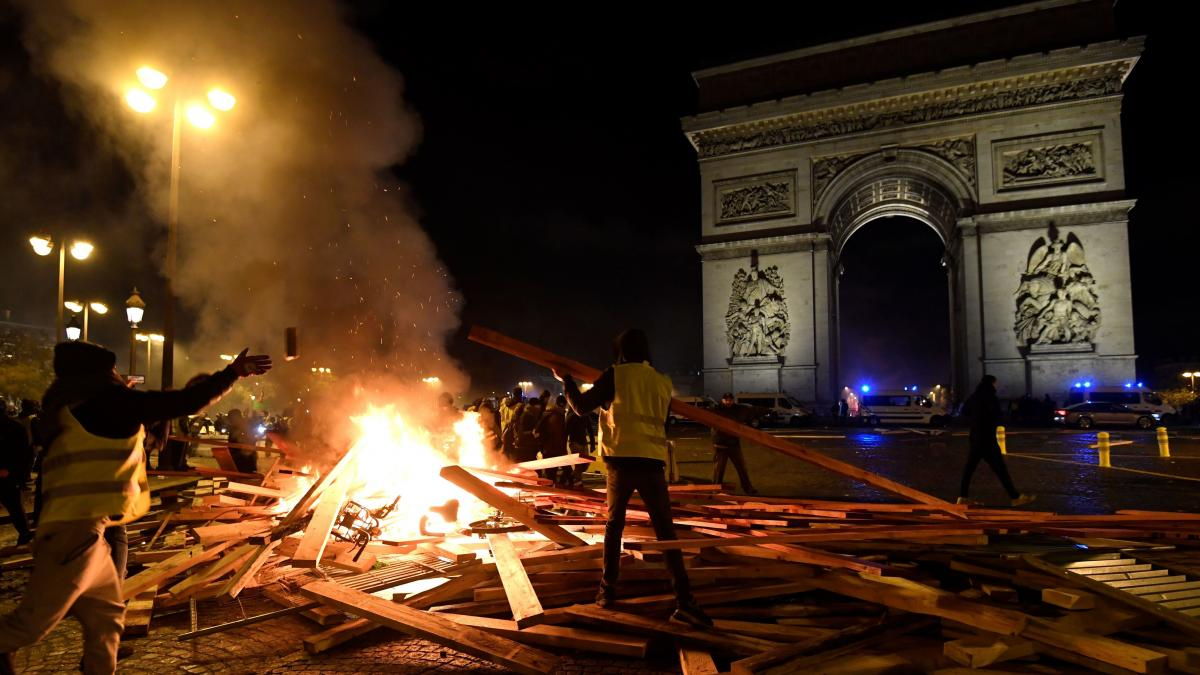 A yellow vest protestor adds to a fire near The Arc de Triomphe in Paris on Saturday, during a rally against a gas tax that will go into effect in January.