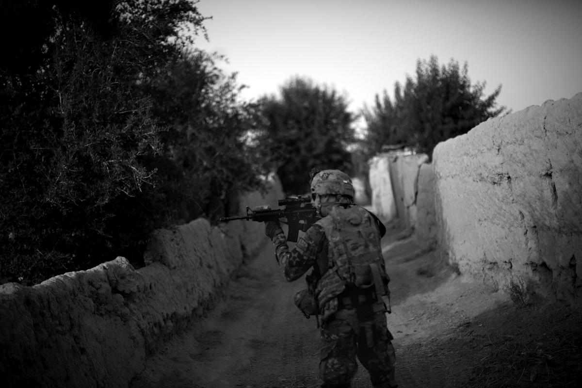 A soldier from the 4th Battalion, 9th Infantry Regiment, Manchus, looks toward the tree line through his rifle scope while on a foot patrol to visit Afghan Local Police in the Panjwai District of Kandahar province in southern Afghanistan. Panjwai is one o