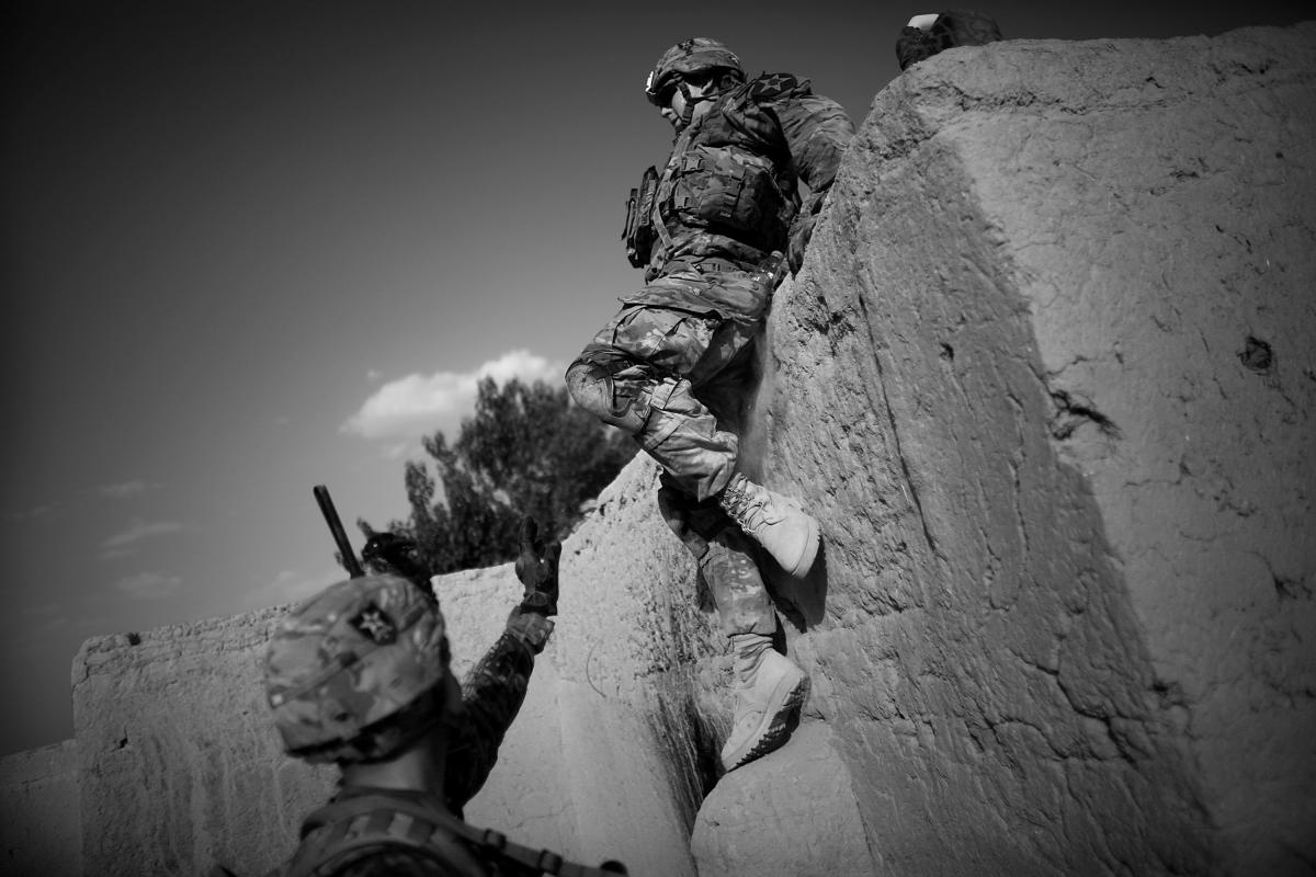 Soldiers help one another off the mud brick wall of a compound while visiting an Afghan Local Police outpost in Panjwai. As American troops draw down in Afghanistan, they are relying more and more on the Afghans to take over security duties.