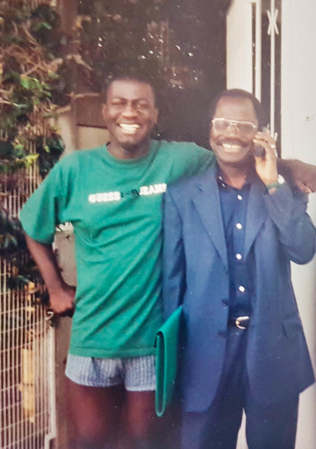 Carl Manlan at 22 with his dad the doctor, Kassi Manlan, in a photo from 2000. Kassi died the next year.