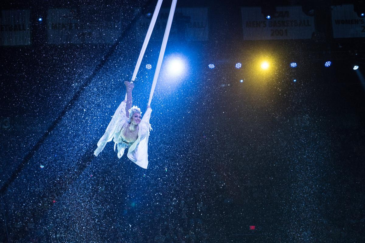 A performer soars through the air. The show features classic acts including clowns and tightrope walkers, as well as stunt motorcyclists and acrobatic ice skaters.