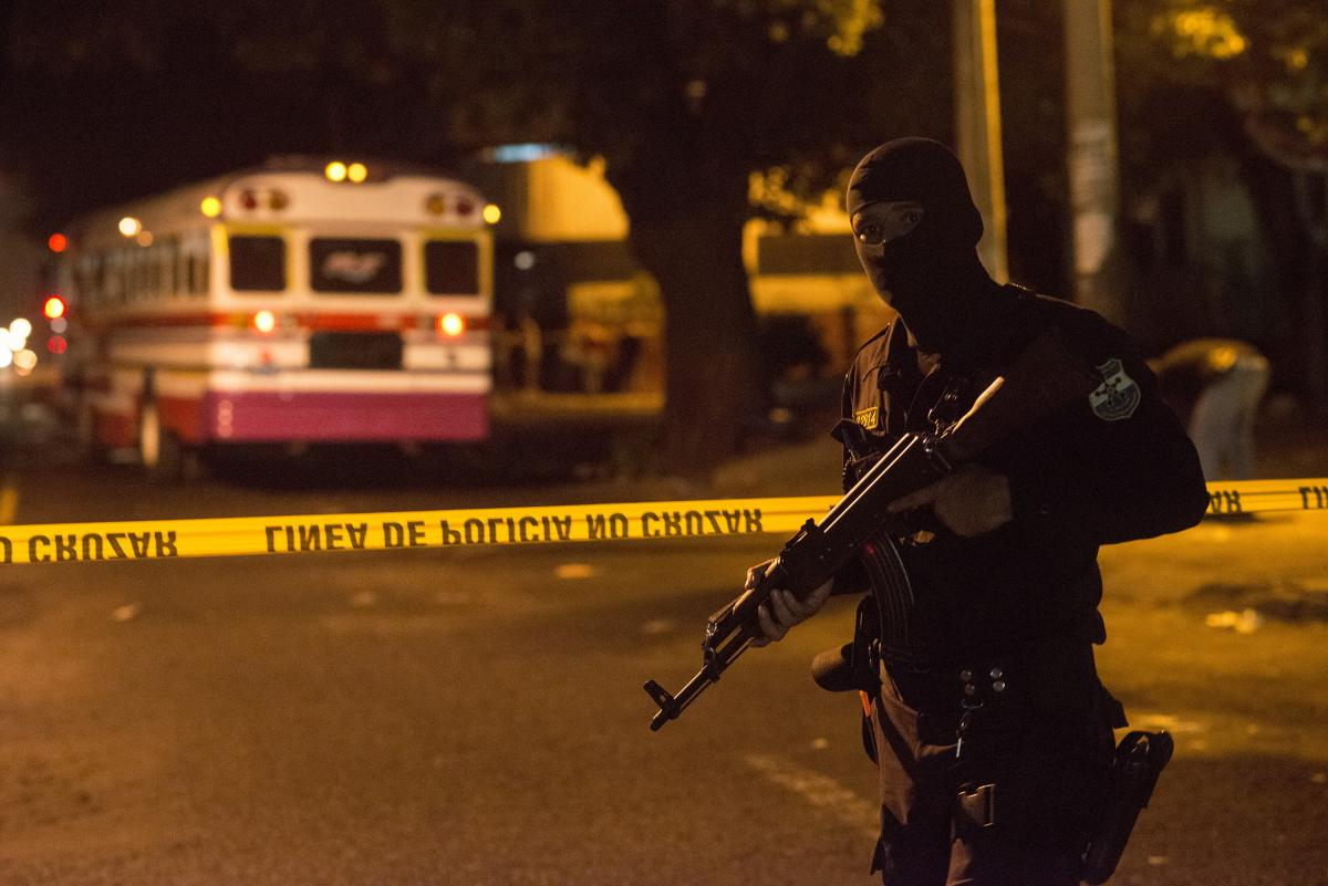 A police officer stands guard after the murder of a bus driver in San Salvador.