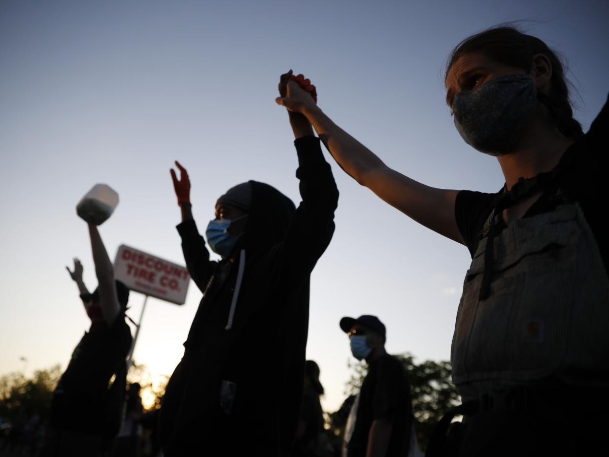 Demonstrators join hands on Thursday, May 28, 2020, in St. Paul, Minn. Protests over the death of George Floyd, a black man who died in police custody, broke out in Minneapolis for a third straight night.