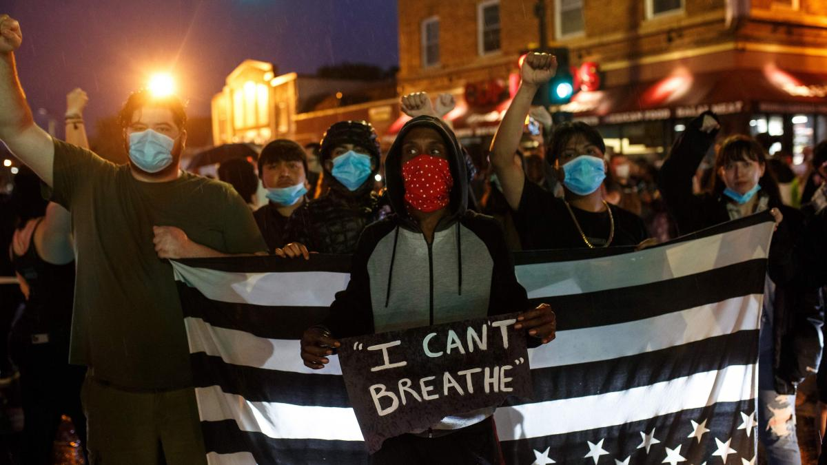 Protesters gather Tuesday near the spot where George Floyd died in police custody in Minneapolis. One of them displays Floyd's final words, which were already made famous by the death of Eric Garner nearly six years earlier.