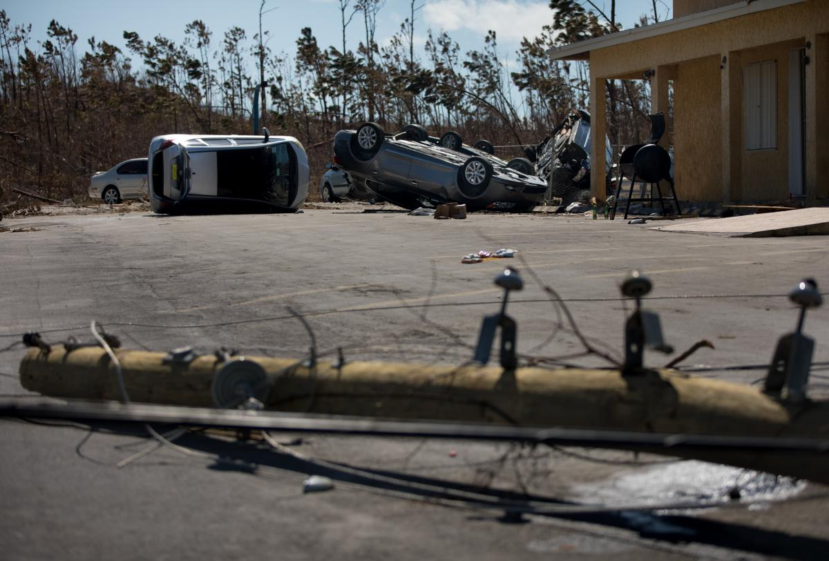 Cars lie overturned and electric poles were down at Bargain Car Rentals in Marsh Harbour a week after Hurricane Dorian destroyed wide swaths of the town.