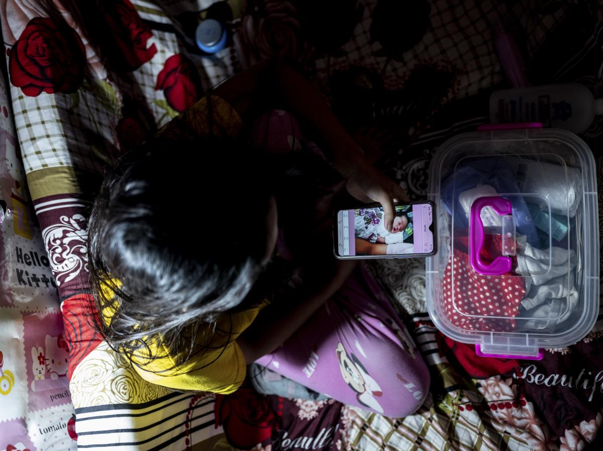 Jianne looks at a photo of her newborn son, whom she placed for adoption. The 21-year-old made the decision because she feared she could not provide for him during the pandemic. July 10. Nueva Vizcaya, Philippines.