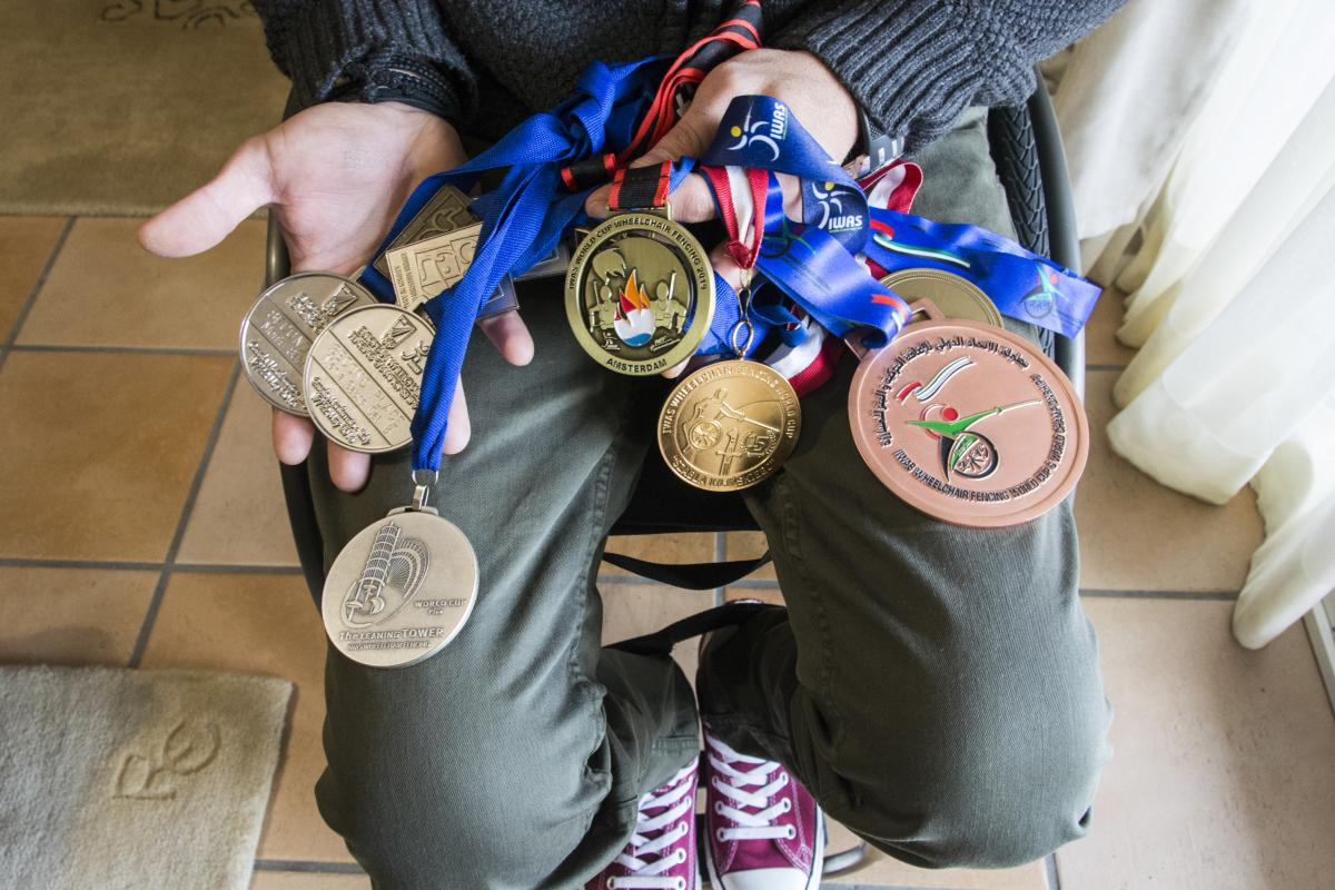 Triantafyllou shows some of the medals he's won over the years, including the gold he won last November at the Wheelchair Fencing World Cup in Amsterdam.