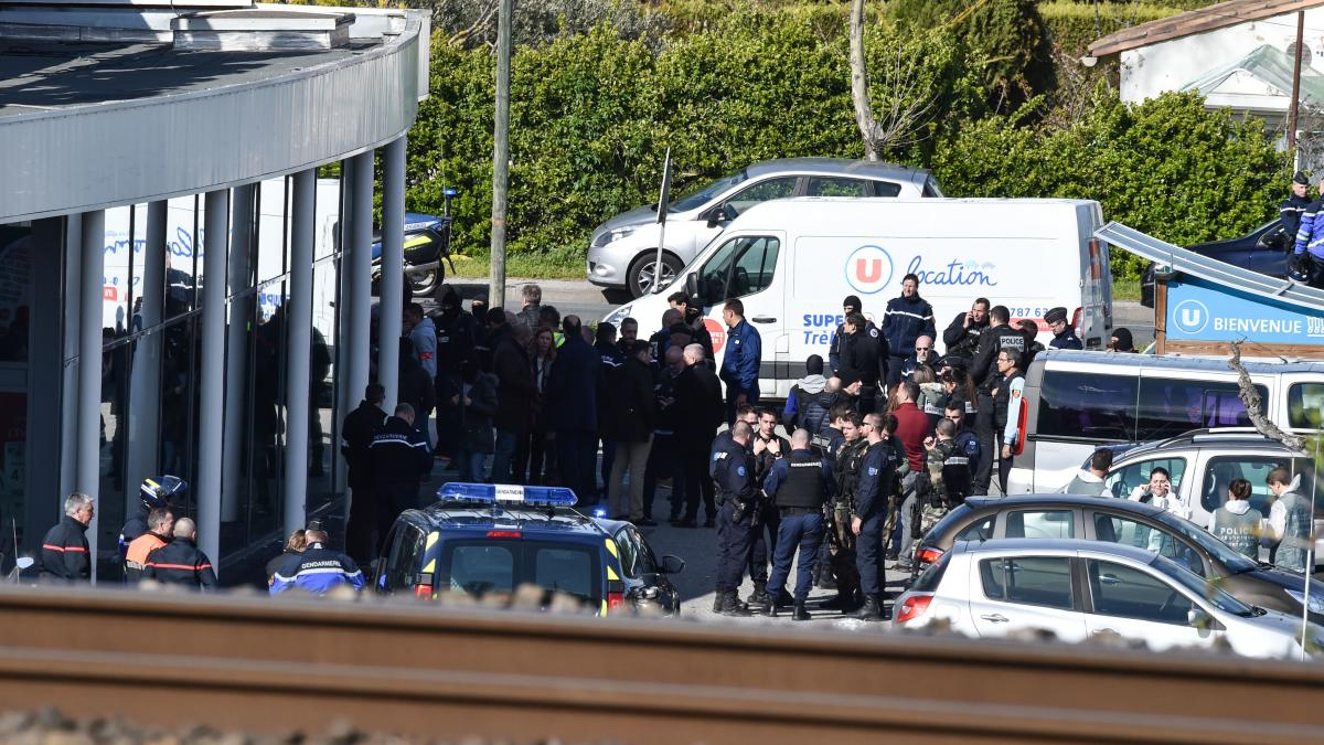 French law police and security forces gather outside the Super U supermarket in the town of Trebes in southern France. A man took hostages before he was killed by security forces on Friday.