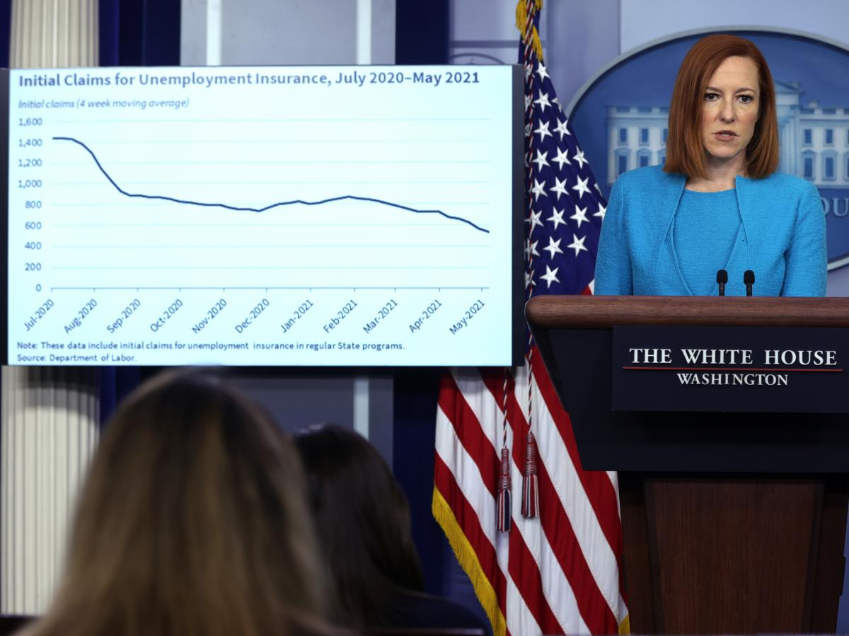 White House press secretary Jen Psaki addresses a news briefing last month as a chart showing a drop in initial claims for unemployment insurance appears on a monitor.