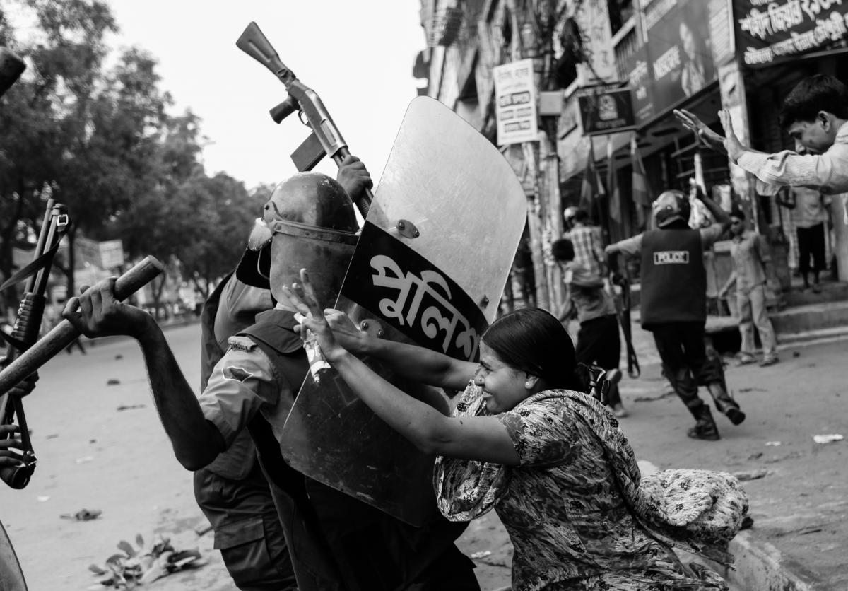 Rahela Akhter, a Bangladeshi garment worker, tries to resist beating from a police officer in riot gear during a protest in Dhaka, June 2010. Dozens of garment workers were injured in clashes with police when they took to the streets demanding higher wage
