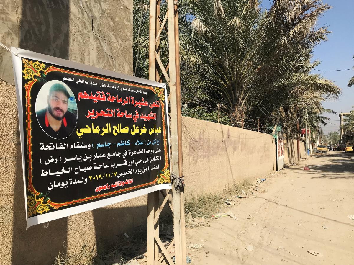 A funeral banner announcing the death of Abbas Salih is displayed on the street of his family's home in Baghdad. Along with more than 300 others killed in recent protests, he is praised as a martyr.