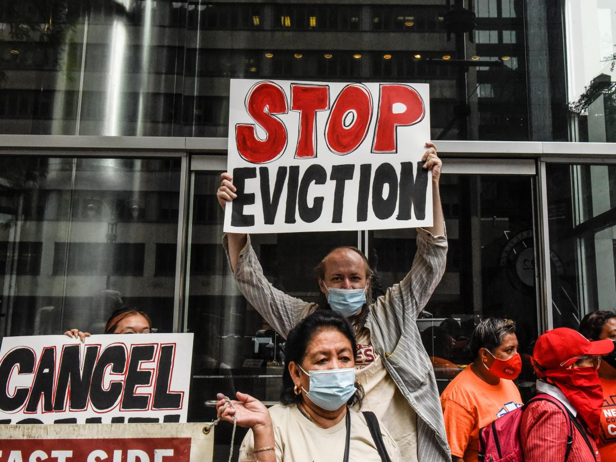 People hold signs opposing evictions on Thursday in New York City.