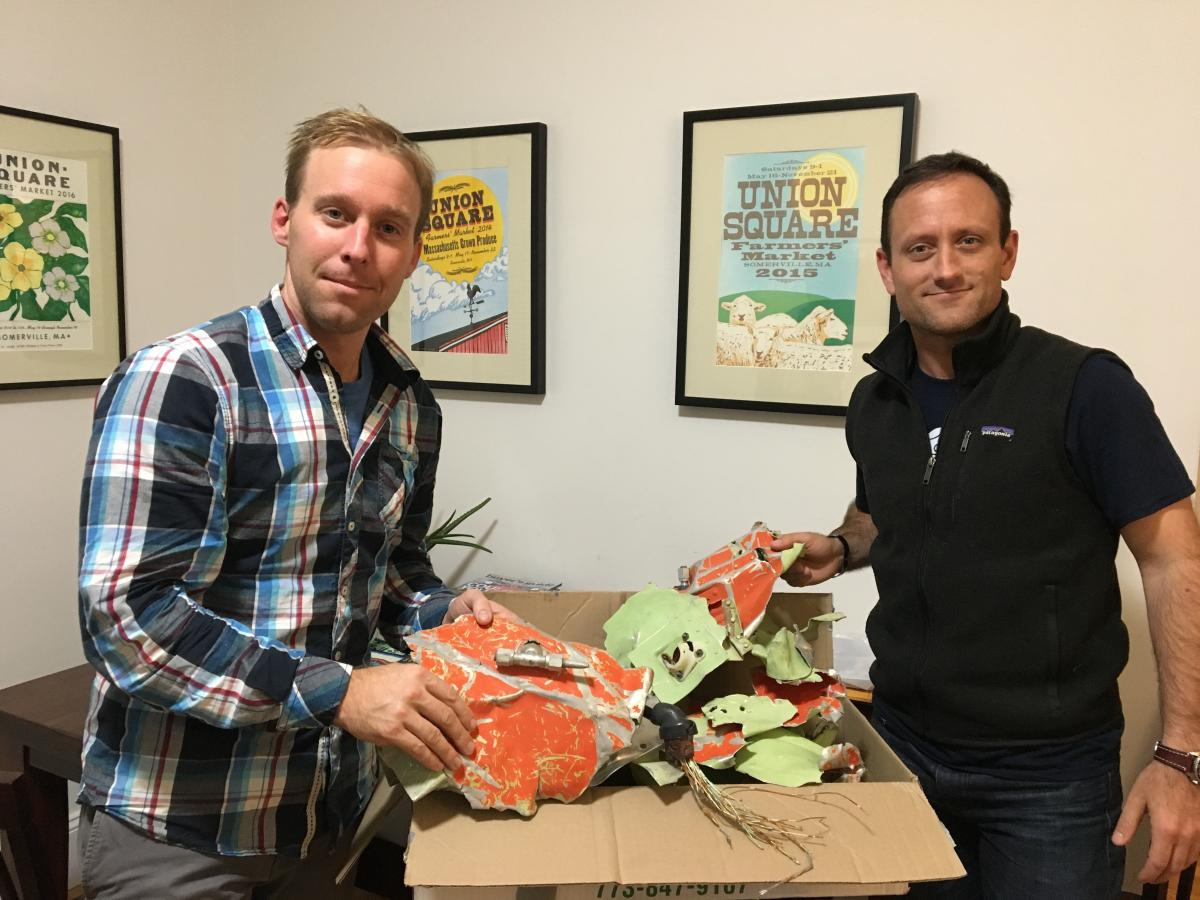 Isaac Stoner (left) and Dan Futrell, with a box of plane parts at Futrell's Somerville apartment.