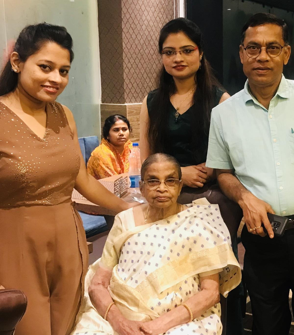 Manas Ray's brother, Kajal, and their mother, Bandana, seated in front. Kajal and his twin daughters, Puja and Lija, (standing) and a nurse (seated in background) have helped care for Bandana in Bardhaman, India.