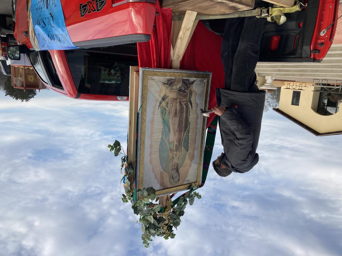 The Rev. Julio Martinez attaches decorations with a hammer to the portrait of Our Lady of Guadalupe mounted in the bed of the truck.