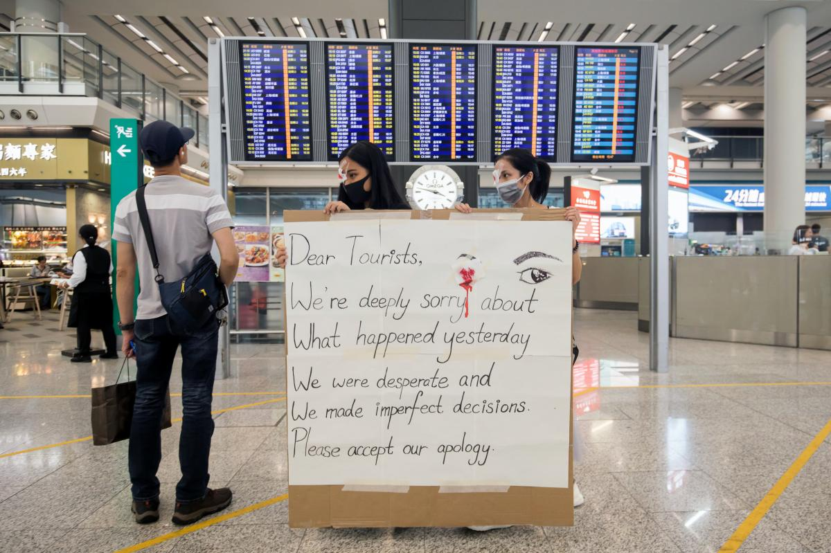 Demonstrators hold a sign apologizing to tourists at the Hong Kong International Airport on Wednesday.